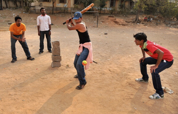 Indian youths play street cricket, local
